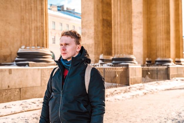 Een jonge man loopt in het centrum van sint-petersburg, in de winter langs de kazankathedraal