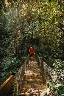 Een jonge man loopt langs een prachtige houten brug in het cerro azul meambar national park (panacam) aan het yojoameer. honduras