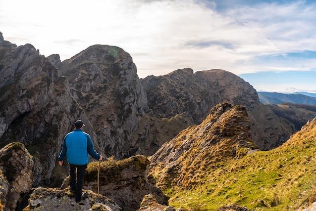Een jonge man loopt op de top van de berg aiako harria