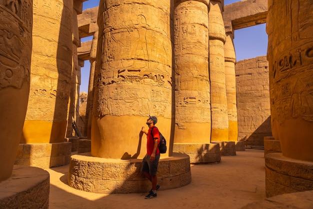 Een jonge man loopt tussen de kolommen met hiërogliefen in de karnak-tempel. egypte
