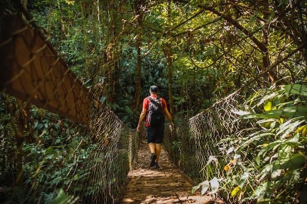 Een jonge man lopen langs een prachtige houten brug in het cerro azul meambar national park (panacam) op lake yojoa. honduras