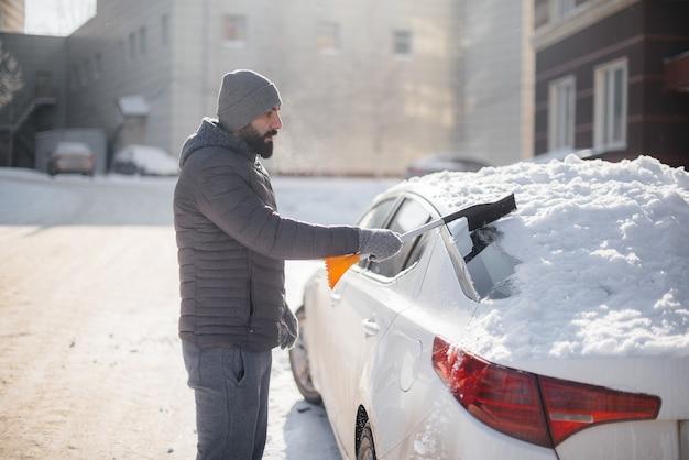 Een jonge man maakt zijn auto schoon na een sneeuwval op een zonnige, ijzige dag.