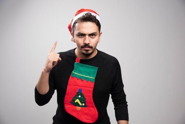 Een jonge man met de hoed van de kerstman met een vinger omhoog met een kerstsok.