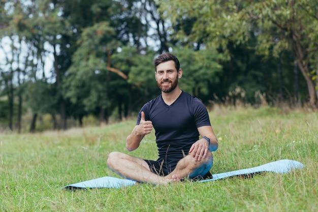 Een jonge man met een baard die in het park op een mat zit, mediteert, doet oefeningen om de ademhaling te verbeteren, een actieve levensstijl