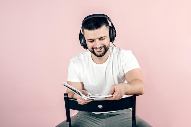 Een jonge man met een baard in een grote zwarte koptelefoon. hobby en vrije tijd.