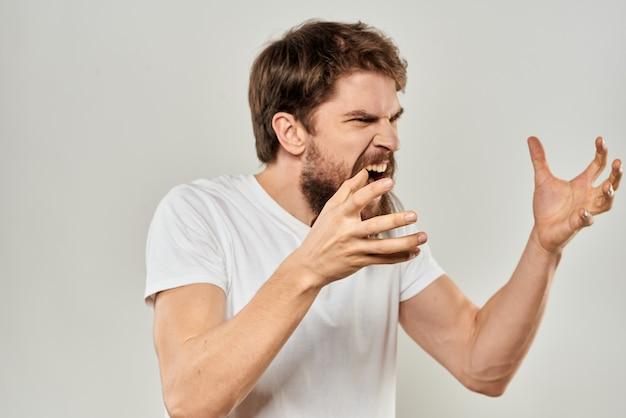 Een jonge man met een baard in een t-shirt toont verschillende emoties, plezier, verdriet, woede in de studio op de achtergrond