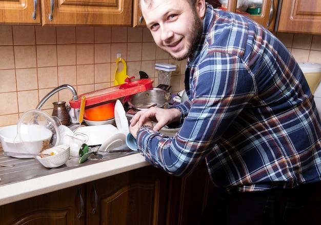 Een jonge man met een baard kijkt op zijn horloge en is blij met de hoeveelheid vuile vaat die in de gootsteen ligt. hij heeft tijd om hem te wassen.