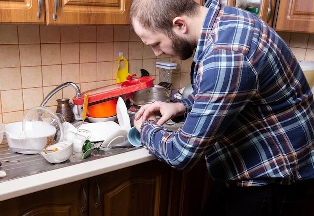 Een jonge man met een baard kijkt op zijn horloge en is geschokt door de hoeveelheid vuile vaat die in de gootsteen ligt