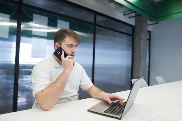 Een jonge man met een baard werkt op een laptop en praat via de telefoon.