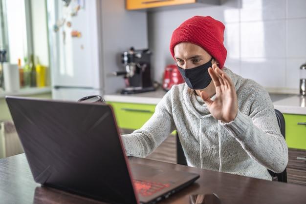 Een jonge man met een beschermend gezichtsmasker kijkt naar het laptopscherm en zwaait met zijn hand