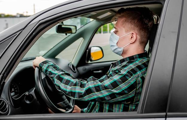 Een jonge man met een beschermend steriel medisch masker zit achter het stuur van de auto. covid-19.