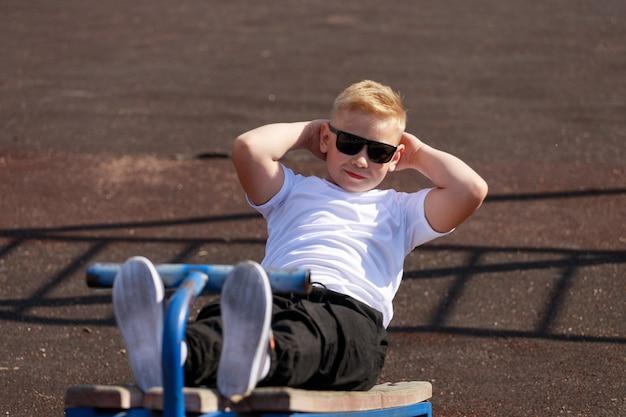 Een jonge man met een donkere bril traint in de zomer de spieren van de pers op het sportveld. hoge kwaliteit foto