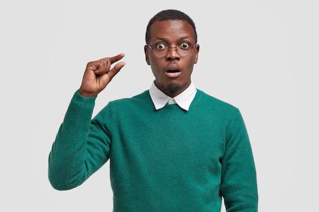 Een jonge man met een donkere huidskleur toont iets kleins, heeft een verbaasde gezichtsuitdrukking, heeft een onverwachte blik, heeft een klein salaris