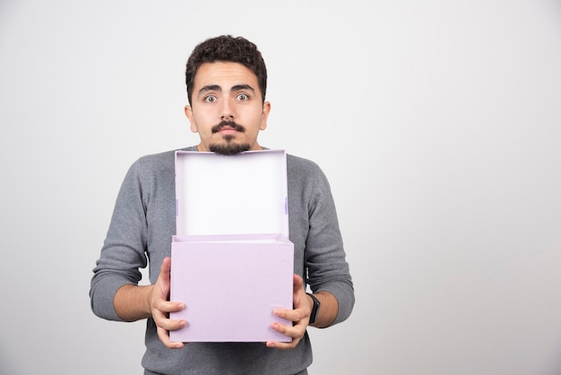 Een jonge man met een geopende paarse doos boven een witte muur.