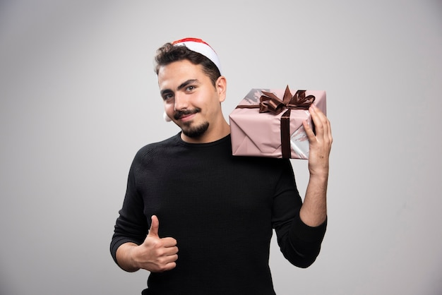 Een jonge man met een geschenkdoos boven een grijze muur.
