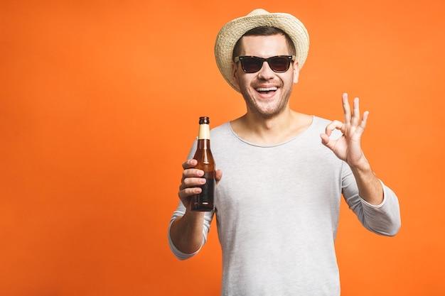 Een jonge man met een hoed en zonnebril geïsoleerd op een oranje achtergrond houdt een flesje bier