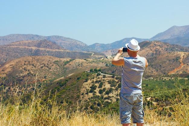 Een jonge man met een hoed in de bergen die foto's maakt van het landschap op een mobiele telefoon