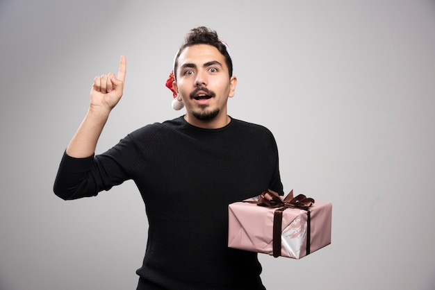 Een jonge man met een kerstmuts toont een vinger en houdt een geschenk vast.