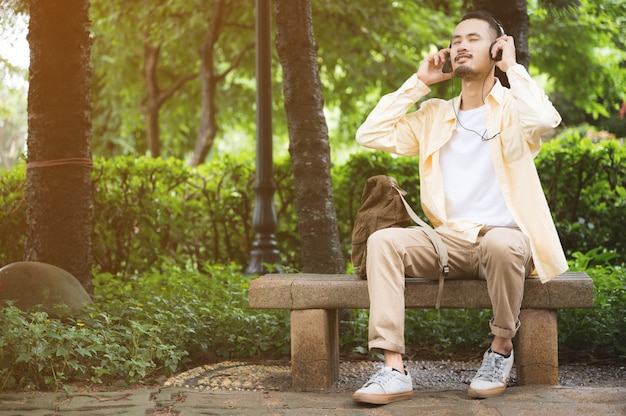 Een jonge man met een koptelefoon en een tablet in het park ontspannen sfeer na een vreselijke ziekte-uitbraak
