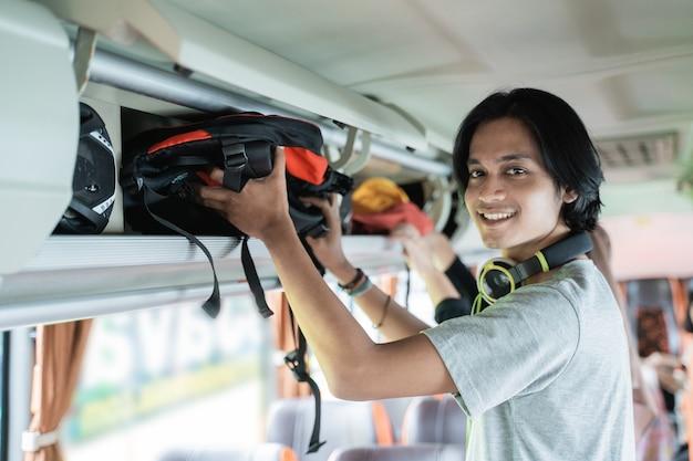 Een jonge man met een koptelefoon glimlacht als hij een tas op een plank zet terwijl hij in de bus staat