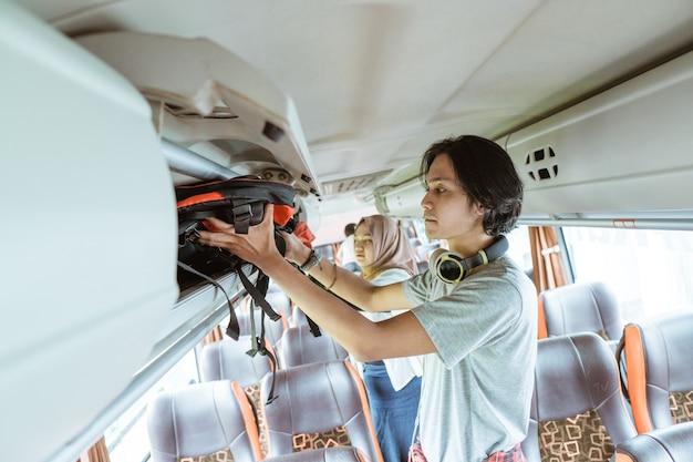 Een jonge man met een koptelefoon zet een tas op een plank terwijl hij in de bus staat