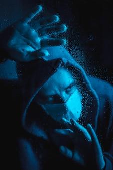 Een jonge man met een masker en een capuchon kijkt uit het raam in de covid19 quarantaine op een regenachtige nacht, met blauw omgevingslicht