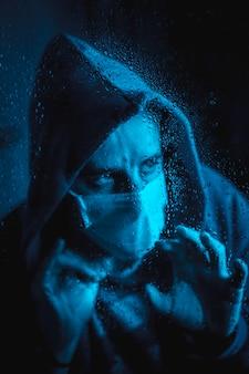 Een jonge man met een masker kijkt uit het raam in de covid19 en plaatst een regenachtige nacht in quarantaine, met blauw omgevingslicht