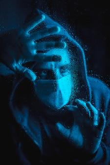 Een jonge man met een masker kijkt uit het raam in de covid19-quarantaine, met blauw omgevingslicht