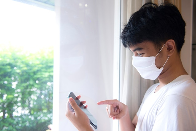 Een jonge man met een masker was thuis om zichzelf in quarantaine te plaatsen