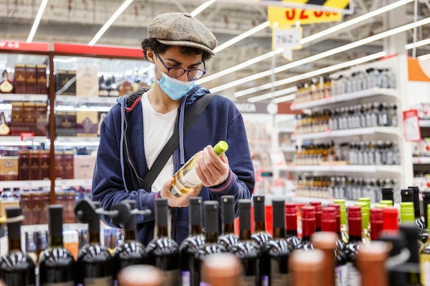 Een jonge man met een medisch masker, een bril en een pet kiest alcohol in de winkel. depressie en vakanties tijdens de pandemie van het coronavirus.