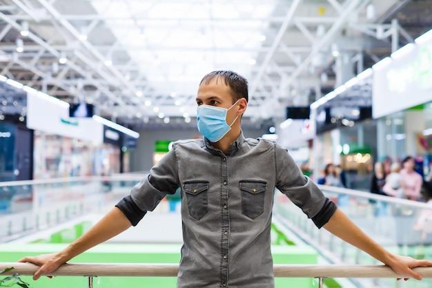 Een jonge man met een medisch masker in een winkelcentrum. de gemaskerde man beschermt zichzelf tegen de epidemie van het chinese virus