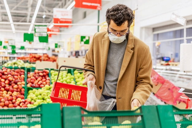 Een jonge man met een medisch masker kiest fruit in een grote supermarkt. voorzorgsmaatregelen tijdens de pandemie van het coronavirus. gezond eten.