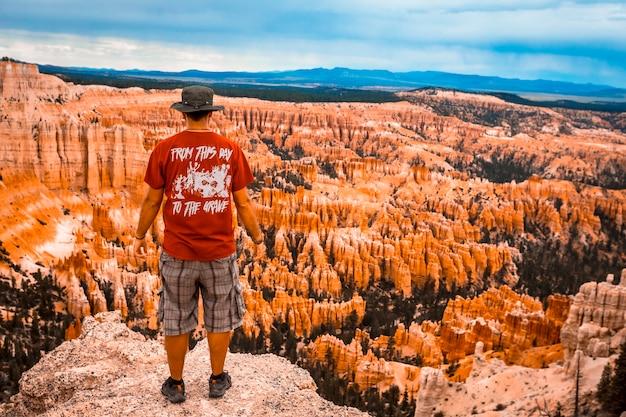 Een jonge man met een rood shirt kijkt vanuit bryce point naar het nationale park