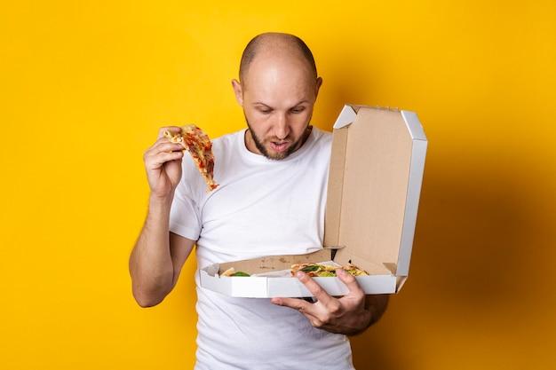 Een jonge man met een stuk pizza kijkt verbaasd naar een pizza in een pakket a