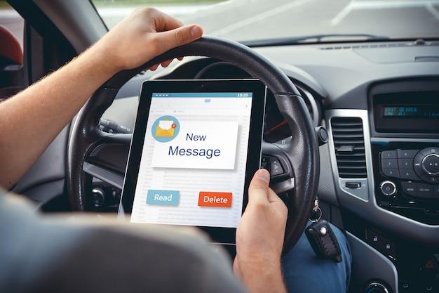 Een jonge man met een tablet in zijn hand aan het stuur van de auto.