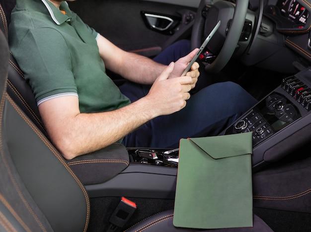 Een jonge man met een tablet in zijn hand bij de sportwagen. multitasking