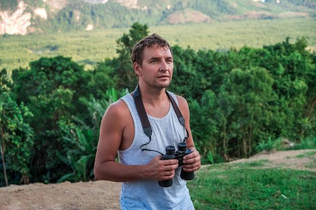 Een jonge man met een verrekijker in zijn handen staat tegen de achtergrond van een wild tropisch bos.
