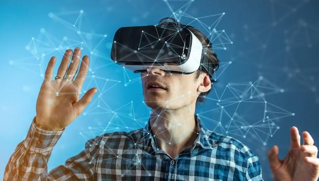 Een jonge man met een virtual reality-bril kijken naar een 3d-visualisatie in een abstract veelhoekig raster op een blauwe achtergrond in een futuristische stijl