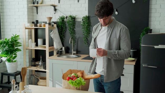 Een jonge man met een zak boodschappen controleert en onderzoekt een productbon na het kopen van eten in een kruidenierswinkel