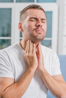 Een jonge man met gesloten ogen houdt zijn pijnlijke keel vast