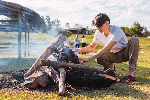 Een jonge man met het witte overhemd en de veldbroek steekt het rustieke houten vuur aan. haar vrienden genieten van een typische landelijke middag in de buitenlucht.