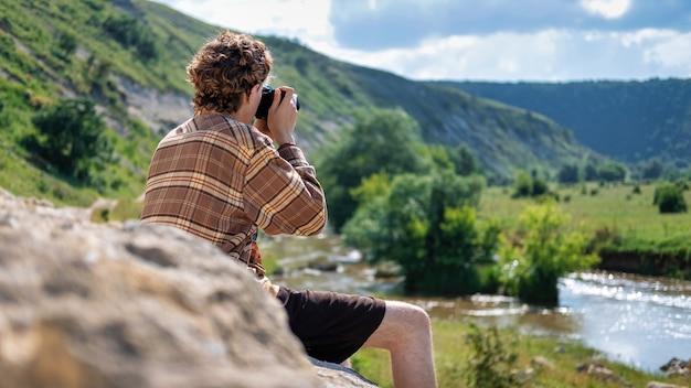 Een jonge man met krullend haar die foto's maakt met een camera in de natuur, zittend op een rots