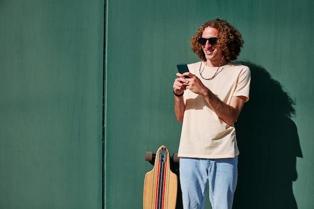 Een jonge man met krullend haar en een zonnebril die een smartphone gebruikt met zijn skateboard