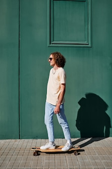 Een jonge man met krullend haar en zonnebril met een groene muur achter hem op een zonnige dag