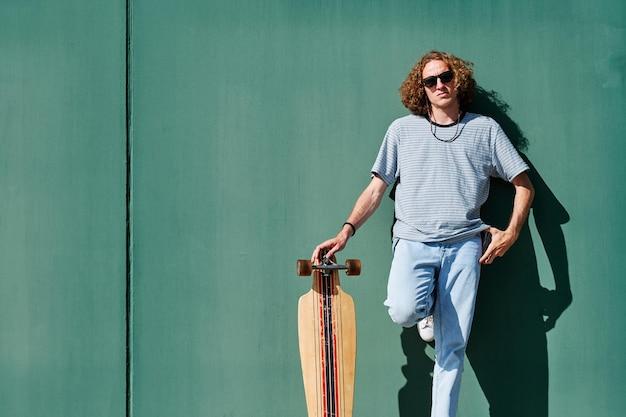 Een jonge man met krullend lang haar en een zonnebril met een longboard of skate met een groene muur achter hem