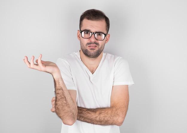Een jonge man met uitgestrekte armen, schouderophalend, zegt: ik weet het niet. geïsoleerd op een grijze achtergrond.