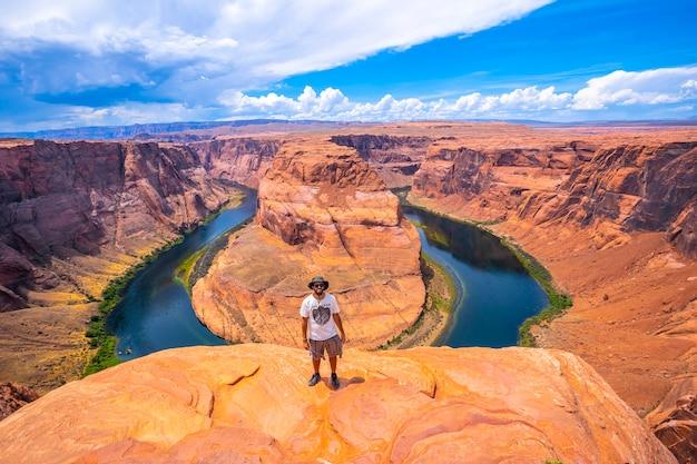 Een jonge man met wit overhemd, groene hoed en camera kijkt in horseshoe bend en de colorado-rivier op de achtergrond, arizona. verenigde staten