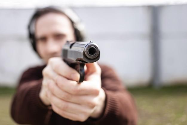 Een jonge man mikt op een pistool. een man met beschermende koptelefoons.