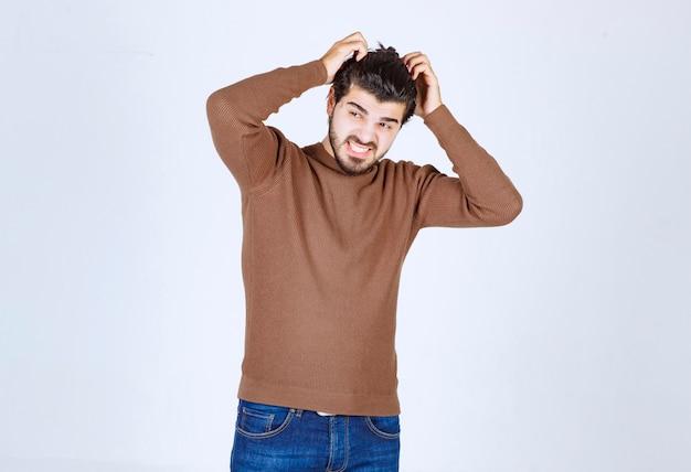 Een jonge man model in bruine trui staan en zijn hoofd krabben. hoge kwaliteit foto