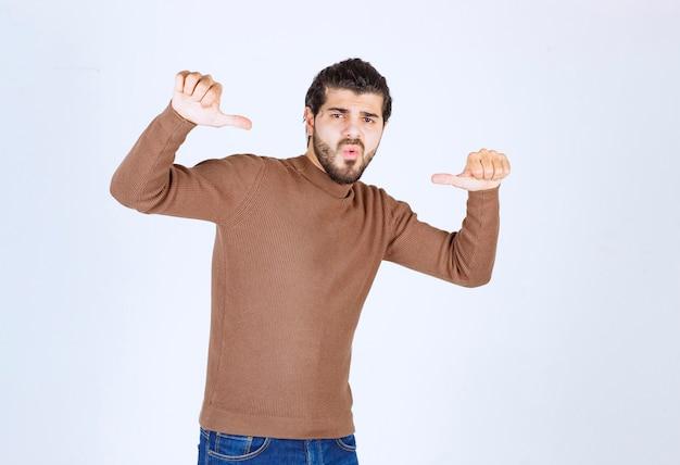 Een jonge man model staat en wijst naar zichzelf.